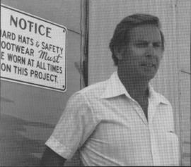 Charles Quick, construction supervisor, in front of safety sign for bridge construction workers