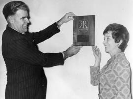 George Ruttan and woman admiring plaque at real estate company