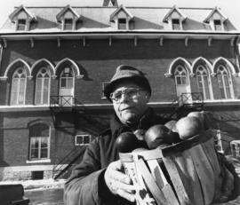 Man with objects standing in front of a building in Belleville, Ontario.