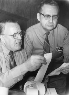 Two men wearing glasses looking over receipts in Belleville, Ontario.