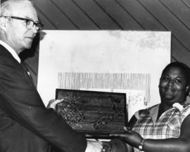 "Unidentified man and woman with a thank you Plaque that says ""Thank You From Grenada"", ..."