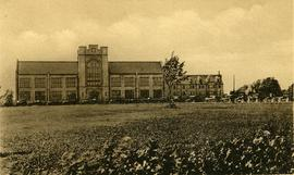 A postcard of the new Albert College, Belleville, Ontario, with a line of cars outside.